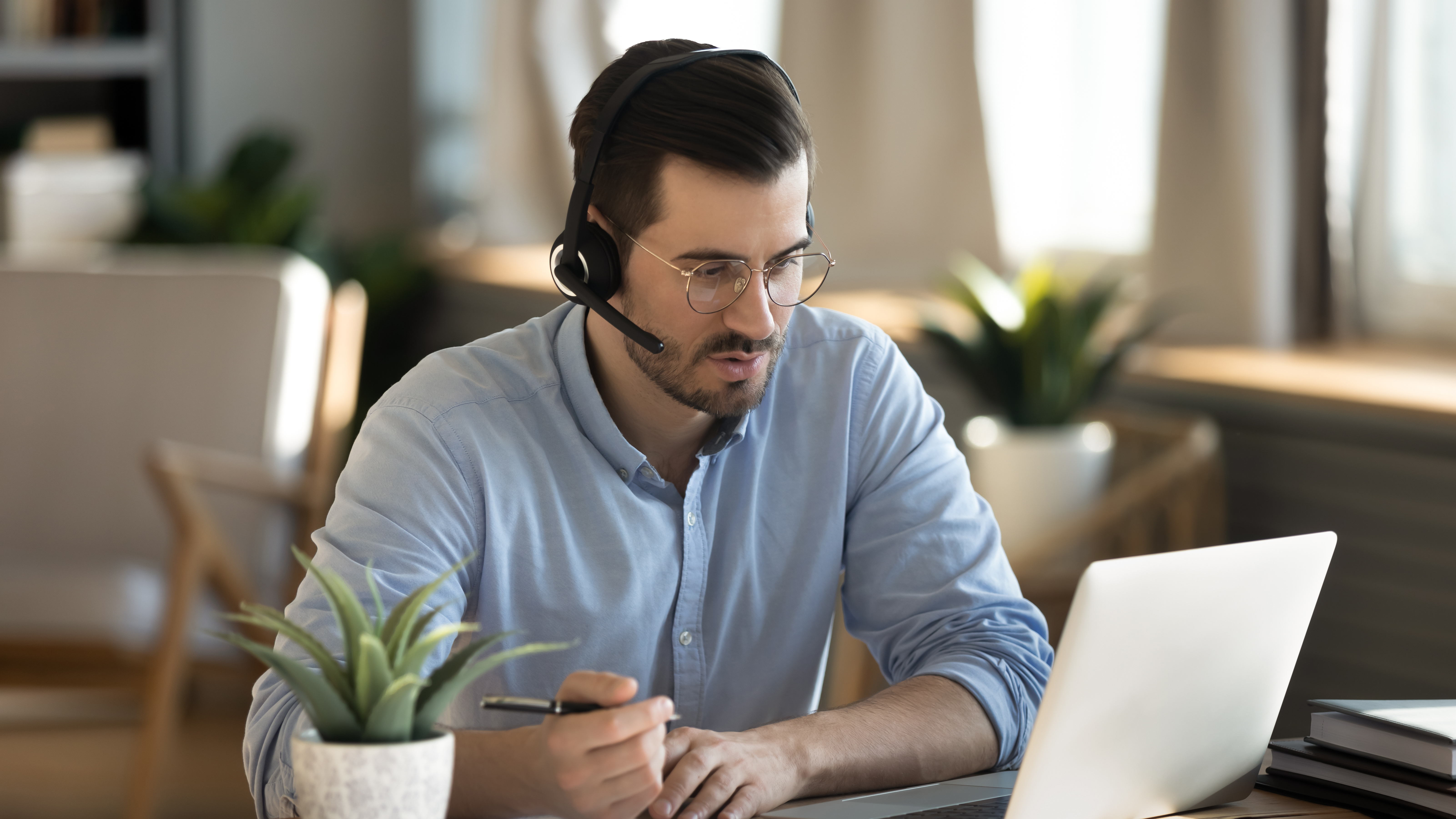 Focused man wearing headset writing notes, studying online